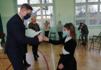 Prezydent wręcza dyplom uczennicy i przybija żółwia