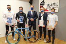Prezydent pozuje do zdjęcia ze sportowcami i rowerem