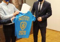 Prezydent pozuje do zdjęcia z niebieską koszulką z okazji zdobycia mistrzostwa