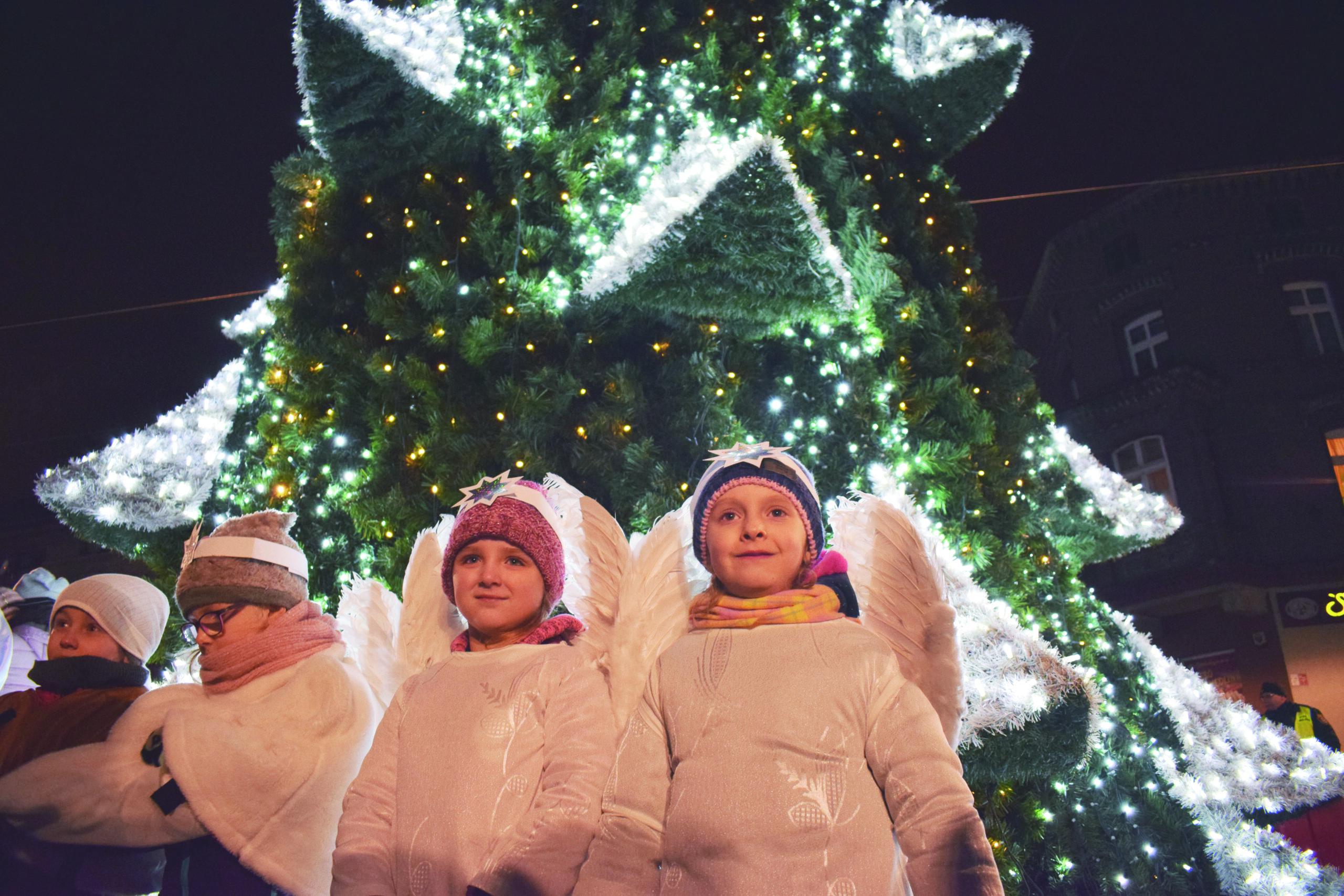 świątecznie udekorowana choinka a wokół niej dzieci