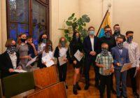 Sportowcy stoją z dyplomami i statuetkami przy prezydencie w reprezentatywnej sali