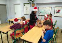 Nauczyciela w czapce Mikołaja rozdaje słodycze